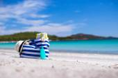 Stripe bag, straw hat, sunblock and towel on white tropical beach — Stock Photo