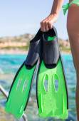Diving goggles, snorkel and snorkeling fins at woman hands — Stock Photo