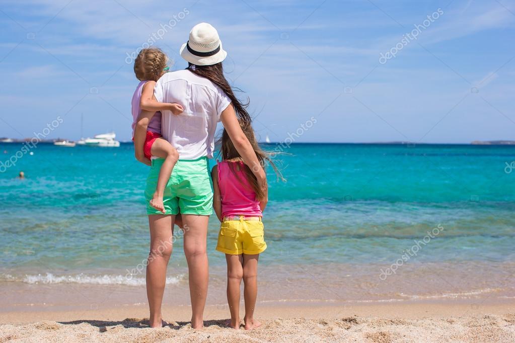 年轻的母亲和两个她的小女孩在异国风情的沙滩上阳光灿烂的日子
