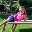 Adorable little girl on beach lounger outdoors — Stock Photo #53956139