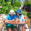 Young couple with smartphone in outdoor cafe — Stock Photo #53956469