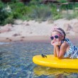 Little girl enjoying swimming in yellow kayak in the clear turquoise water — Stock Photo #53956513