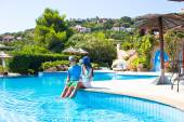 Young happy romantic couple relaxing by swimming pool — Stock Photo
