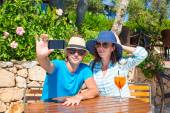 Young couple taking photo with smartphone in outdoor cafe — Stock Photo