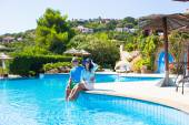Lovely young romantic couple relaxing by swimming pool — Stock Photo