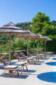 Wooden deck chairs and umbrellas near infinity pool in luxury resort — ストック写真