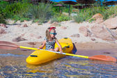 Little cute girl enjoy swimming on yellow kayak in clear turquoise water — Stock Photo