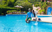 Young romantic couple near swimming pool at exotic resort — Stock Photo