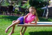Adorable little girl on beach lounger outdoors — Stock Photo