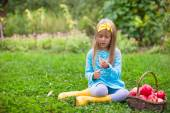 Little girl with basket of apples in sunny autumn day — Stock Photo