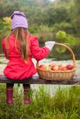 Rear view of young girl sitting on bench and holding large basket with red apples — Stock Photo