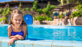 Cute happy little girl in the swimming pool — Stock Photo