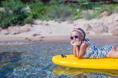 Little girl enjoying swimming in yellow kayak in the clear turquoise water — Stock Photo