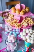Marshmallow, sweet colored meringues, popcorn, custard cakes and white cake pops on festive table — Stok fotoğraf