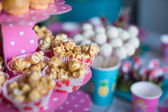 Portion popcorn on kids party on sweet dessert table — Stock Photo