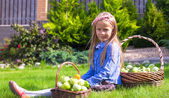 Adorable little girl with autumn harvest of tomato on the lawn — Foto Stock