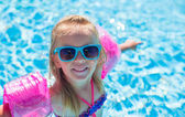 Adorable happy little girl have fun in the swimming pool — Stok fotoğraf