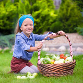 Portrait of little girl with autumn harvest of tomato in baskets — Foto Stock