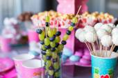 Canape of fruit, white chocolate cake pops and popcorn on sweet childrens table at birthday party — Stock Photo