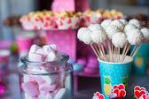 Malvavisco, merengues, palomitas de maíz, tortas de crema y pastel de color dulce aparece en mesa — Foto de Stock