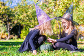 Adorable little girls in witch costume casting a spell on Halloween — Stock Photo