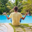 Young man sitting in lotus position near the pool — Stock Photo #56087475