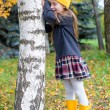 Little girl playing hide and seek in autumn forest outdoors — Stock Photo #56087665