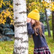 Little girl playing hide and seek in autumn forest outdoors — Stock Photo #56087879