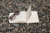 Notepads plans and sunglasses on a gravel road to the sea — Stock Photo