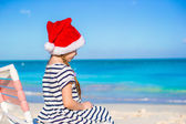 Little adorable girl wearing Santa hat at caribbean beach — Stock Photo