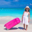 Little adorable girl with big luggage in hands on tropical beach — Stock Photo #56091953