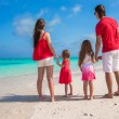 Happy family of four on beach in red Santa hats — Stock Photo #56092063