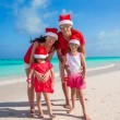 Happy family of four on beach in red Santa hats — Stock Photo #56093637