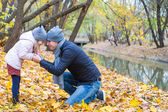 Young father have fun with cute daughter in autumn park — Stock Photo