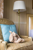 Soft plush toy bunny on a chair in a hotel room — Stock Photo