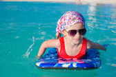 Little adorable girl on surfboard in the turquoise sea — Stock Photo