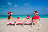 Happy family of four in Christmas Hats on white beach — Stock Photo