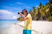 Young man taking pictures on tropical beach — Zdjęcie stockowe