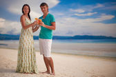 Young romantic couple relaxing with two cocktails on sandy beach — Stock Photo