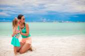 Young beautiful mother and adorable little daughter have fun at tropical beach — Stock Photo