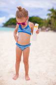 Little cute adorable girl in swimsuit rubs sunscreen herself — Stock Photo