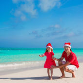 Little girl and happy dad in Santa Hat at exotic beach — Stock Photo