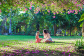 Young mother with little daughter in the lush garden and enjoy summer rest — Stock Photo