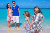 Young family of four with two kids at tropical white beach — Stock Photo