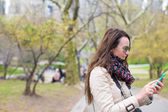 Young woman with a phone in the park outdoors — Stock Photo
