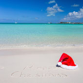 Merry Christmas written on tropical beach white sand with xmas hat — Stock Photo