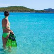 Young woman with snorkeling gear on tropical beach — Stock Photo #56602289