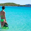 Young woman with snorkeling gear on tropical beach — Stock Photo #56602311