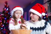 Young dad with little daughter in Santa hat bake gingerbread cookies — Stock Photo