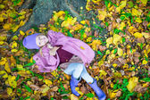 Little adorable girl in autumn park on sunny fall day — Stock Photo